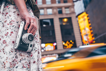 Female hand with a retro camera on Manhattan