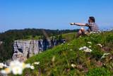 Hiker enjoying breathtaking landscape from top of cliff in Switzerland