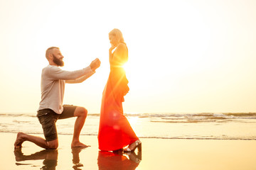 Romantic marriage proposal at the seaside at sunset on the beach sea. Young couple in love female said yes to offer of marriage February 14, St. Valentine's Day
