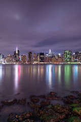 View on Midtown manhattan from east river with rocks on foreground at night,long exposure shot