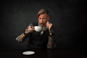 Porträt eines bärtigen Mannes mit einem Tasse Kaffee, vor dunklem Hintergrund