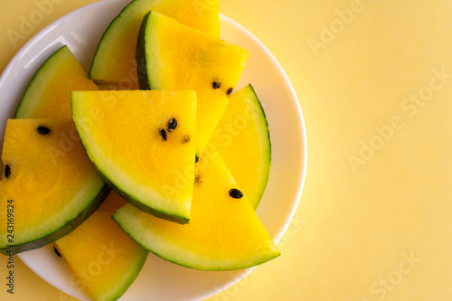Ripe fresh slices of yellow watermelon in white plate on yellow background. Top view. Copy space.