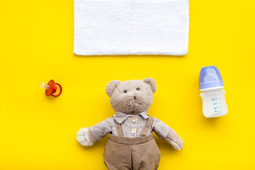 Toys for newborn baby set with teddy bear and milk in bottle on yellow background flat lay space for text © 9dreamstudio