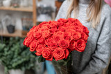 Red roses in glass vases in womens hands. Bunch scarlet red. the concept of a florist in a flower shop. Wallpaper. - 243175030