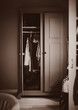 View at wardrobe with clothes in bedroom at Dutch house. . Image in sepia color style