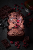 Uncut chocolate cake with pieces of chocolate and red currants on rough gray background - 243177451