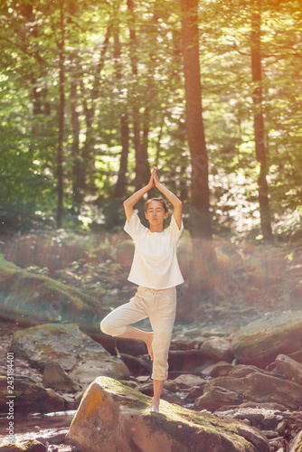 Wall mural Woman practicing yoga in pose of tree in forest.