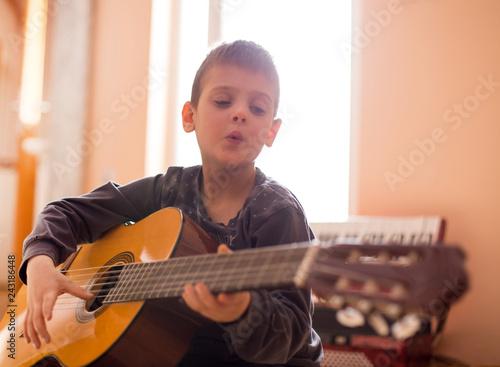 Boy enjoying playing guitar - 243186448