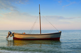 Fishing boats moored near the shore at sunset background - 243187220