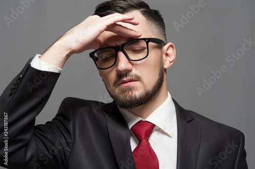 Leinwanddruck Bild Close-up Serious businessman in formal suit and glasses posing on gray background.