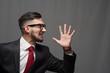 Leinwanddruck Bild - Portrait of an emotional happy shouting businessman or manager posing on gray background