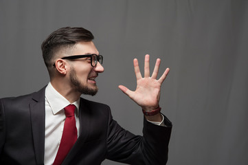 Portrait of an emotional happy shouting businessman or manager posing on gray background