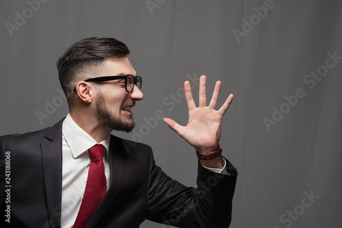 Leinwanddruck Bild Portrait of an emotional happy shouting businessman or manager posing on gray background