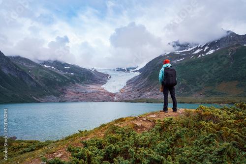 Leinwandbild Motiv Girl tourist looks at a glacier. Svartisen Glacier in Norway.
