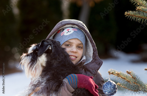 Girl holding dog beside christmas tree