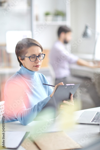Young serious businesswoman in casual light blue pullover making working notes in document in office