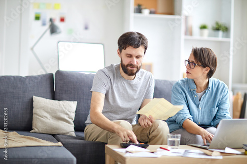 Young man counting family budget and consulting with his wife browsing in the net near by