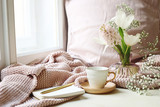 Cozy Easter, spring still life scene. Cup of coffee, opened notebook, pink knitted plaid on windowsill. Vintage feminine styled photo. Floral composition with tulips, hyacinth and Gypsophila flowers. - 243208276