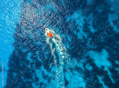 Aerial view of floating speed boat in transparent blue water. Motorboat in the sea in balearic islands at sunset in summer.  Landscape. Top view from drone. Seascape with yacht in motion in bay