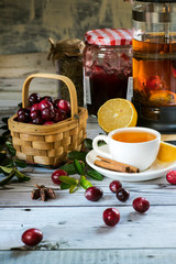 Hot spicy lingonberry or cranberry tea in cup, rustic background