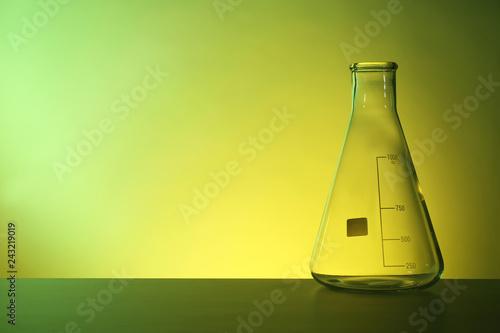 Leinwandbild Motiv Empty conical flask on table against color background. Chemistry laboratory glassware