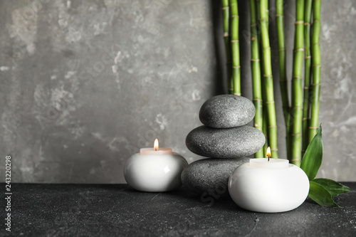 Leinwanddruck Bild Spa stones with candles and bamboo on table, space for text