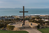 Wooden cross overlooks coastal beach town with lines of perfect waves breaking in the background. - 243224647