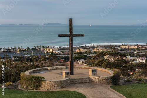 Wooden cross overlooks coastal beach town with lines of perfect waves breaking in the background.