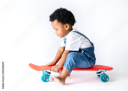 Cute little boy sitting on a skateboard