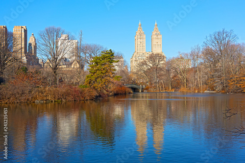 Sunny winter morning in Central Park, New York, USA. Manhattan skyscrapers reflection in a lake waters.