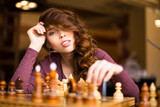 Woman playing chess indoor and thinking position, find winning move, strategy.