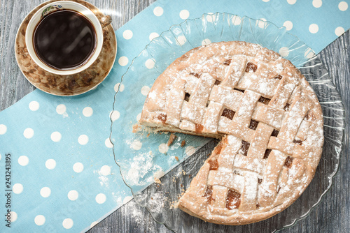 Homemade apple pie with cup of coffee on grey wooden table.