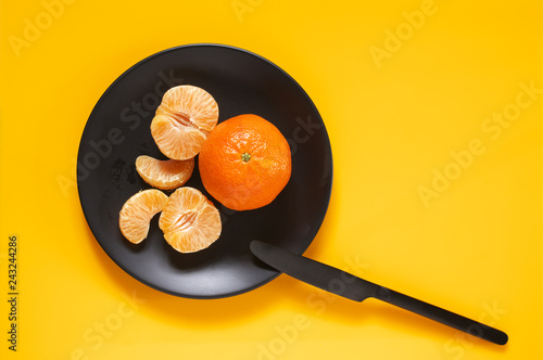 Tangerines in black plate on yellow
