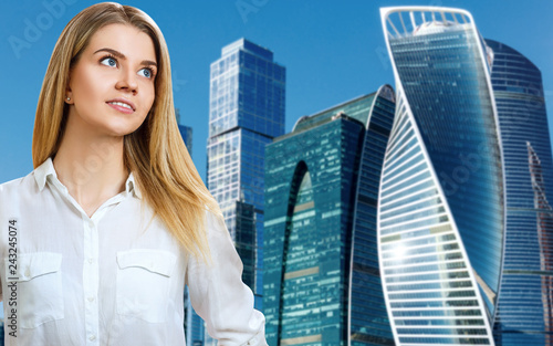 Foto Murales Business woman stands over cityscape background.