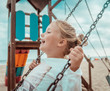 Kind schaukelt am Strand auf dem Spielplatz