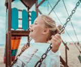 Kind schaukelt am Strand auf dem Spielplatz - 243245431