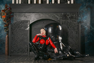 beautiful woman in black latex with red Breasts posing against the fireplace in the Gothic Deluxe room with white candles and big octopus