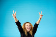 Emotional satisfied young attractive ginger curly woman with opened mouth celebrating and cheering a success raising up hands with the sign of victory on blue background.
