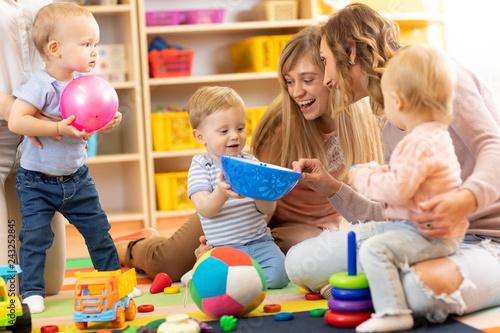 Leinwandbild Motiv Group of happy moms with their babies in nursery