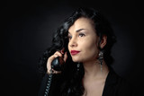Portrait of attractive brunette with old phone on a black bacground. - 243253050