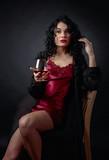Portrait of attractive brunette with glass of brandy on a black background.