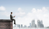 Man on roof edge send message with smartphone and cityscape at background - 243255425