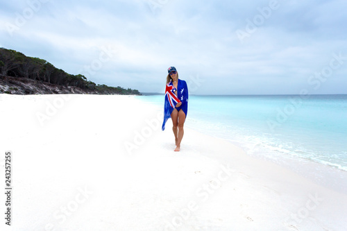 Woman on beach with Aussie flag draped around her