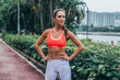 Full-length portrait of sporty fit model standing in park posing in pink sports bra and white leggings with hands on hips.