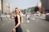 Emotional blonde model with long hair wearing black dress and walking down the sunny street. Empty space - 243261628