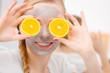 Leinwanddruck Bild - Happy young woman having face mask holding kiwi