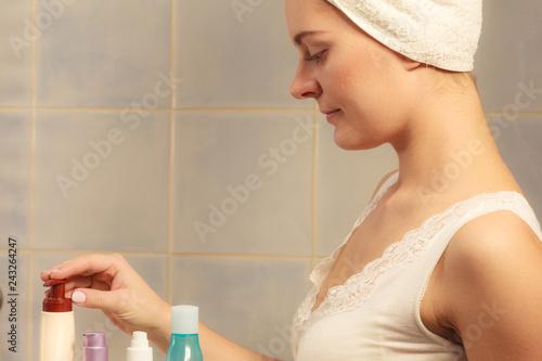 Leinwanddruck Bild Woman in bathroom with bottles cosmetics