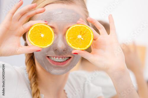Leinwanddruck Bild Happy young woman having face mask holding kiwi