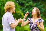 Couple blowing soap bubbles, having fun - 243264605