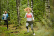 Young sportswoman jogging in the forest with her boyfriend running after her during daily training